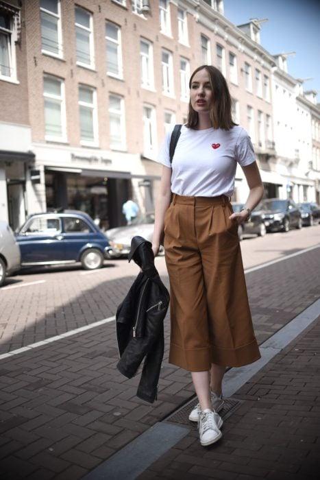 Chica usando unos pantalones estilo culotte con una camisa blanca y tenis, mientras espera parada en la calle