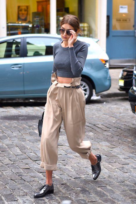 Bella Hadid caminando por la calle mientras usa un pantalón de color beige camisa gris y zapatos de charol