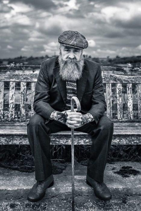 Pip sentado en una banca, sosteniendo un bastón