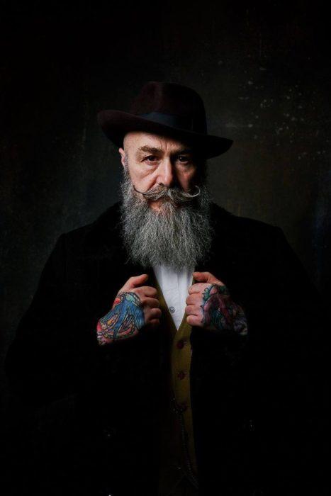 Pip usando traje sastre, posando sus tatuajes para una fotografía