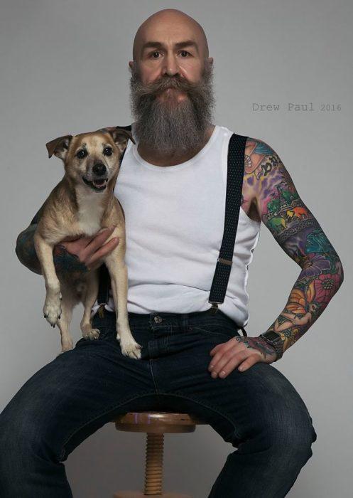 Pip sentado en u banco, cargando un perro, mirando al frente