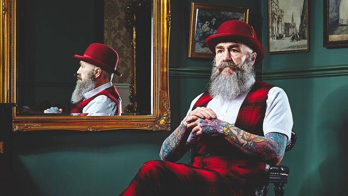 Pip sentado frente a un espejo, usando traje sastre en rojo