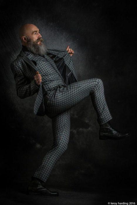 Pip modelando su traje sastre, alzando una pierna, sonriendo