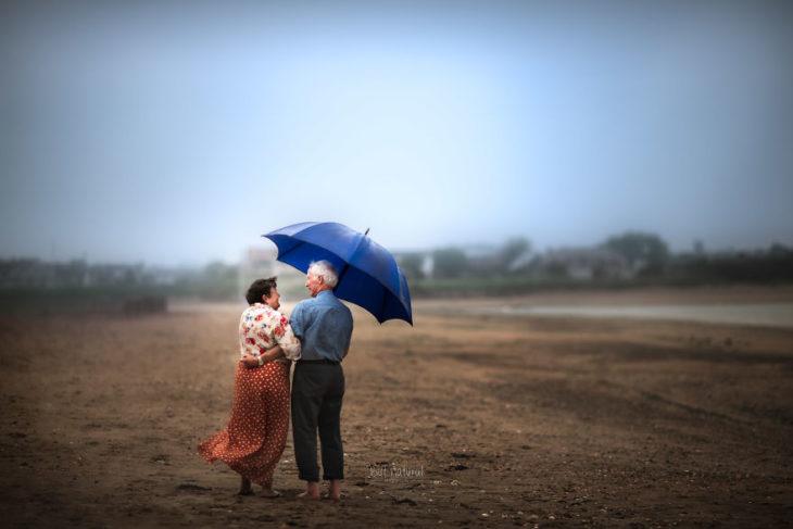 Abuelos caminando del brazo sobre un terreno árido, fotografía de Sujata Setia