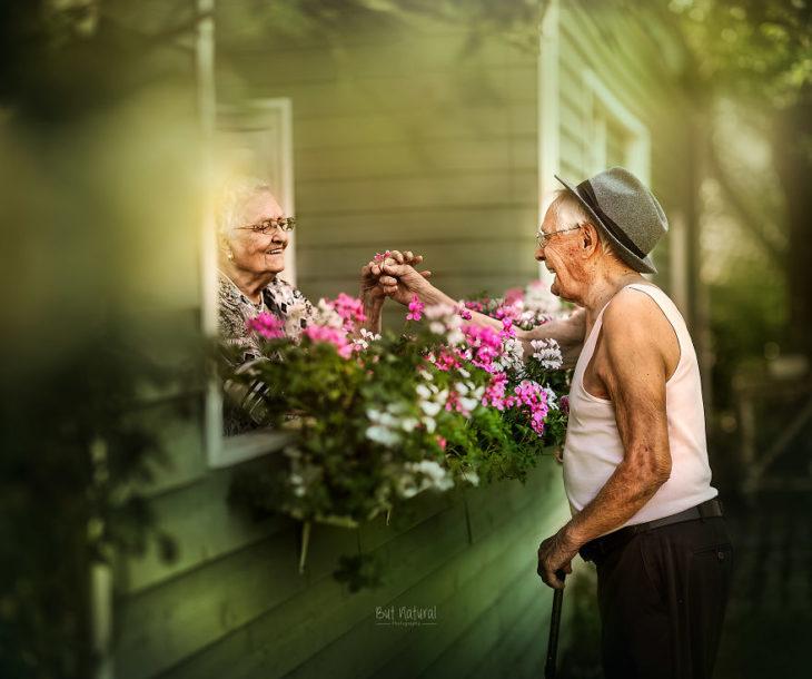 Abuelos platicando a través de una ventana rodeada de flores, fotografía de Sujata Setia