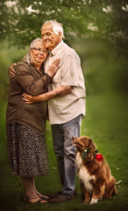 Abuelos junto a su perros parados en un jardín, abrazados, fotografía de Sujata Setia