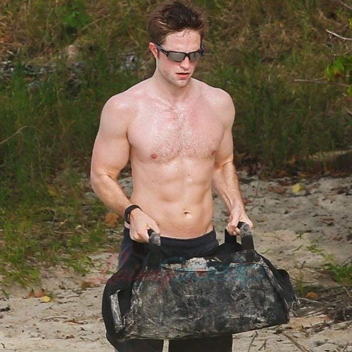 Robert Pattinson entrenando en la playa mientras carga un costal con piedras