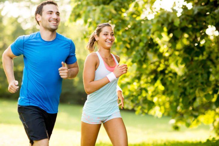 una pareja corriendo en un lugar verde