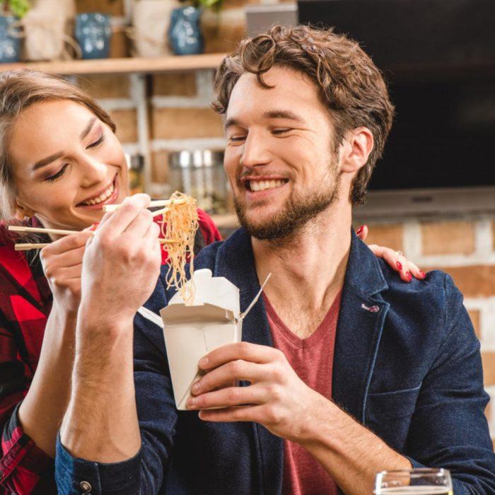 una pareja come pasta de un empaque desechable