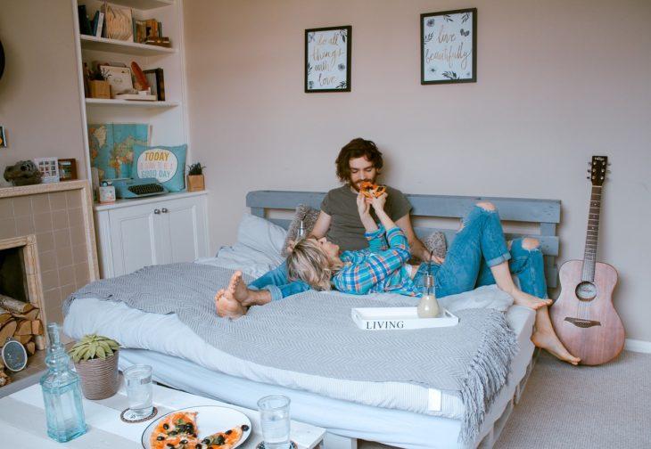 una pareja en una cama come pizza
