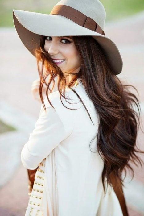 Chica de cabello largo, sonriendo, usando sombrero estilo campesino