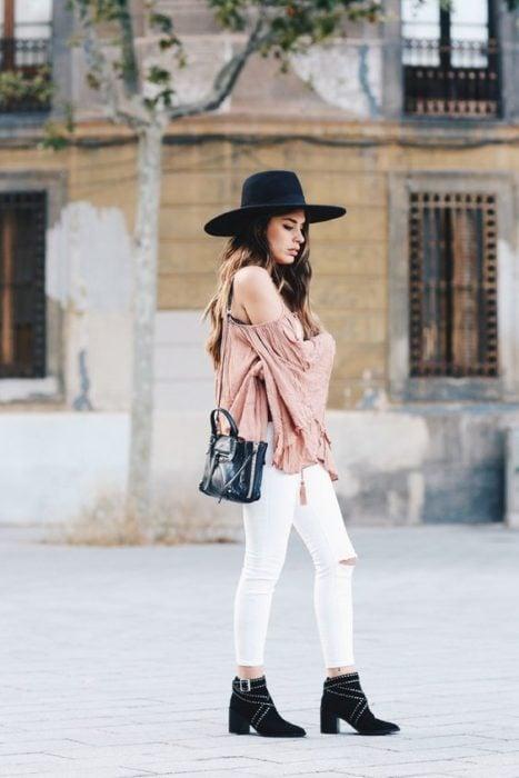 Chica de perfil modalndo su outfit y sombrero color negro