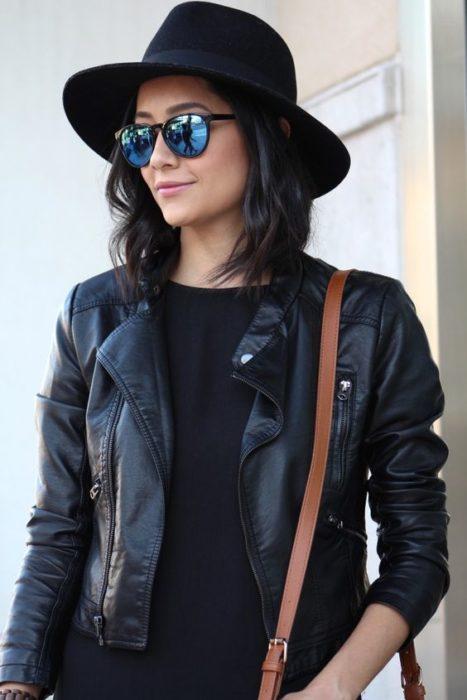 Chica de perfil mostrando sus lentes y usando ropa de cuero en color negro