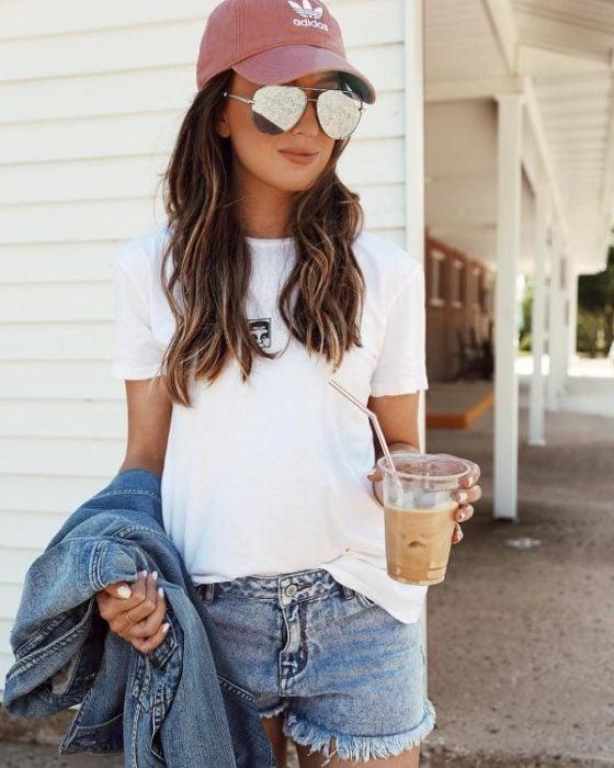 chica usando gorra deportiva y bebiendo agua