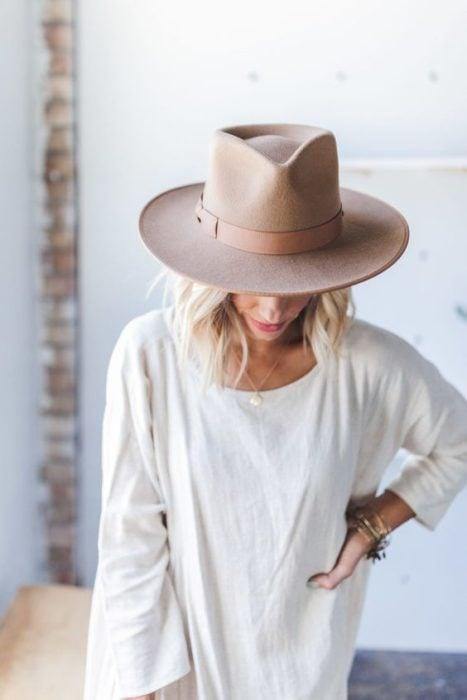 Chica agachada mostrando su sombrero color arena