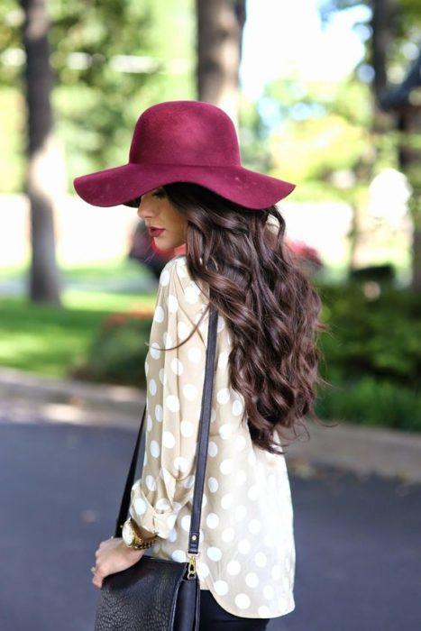 Chica modelando de perfil su sombrero color vino