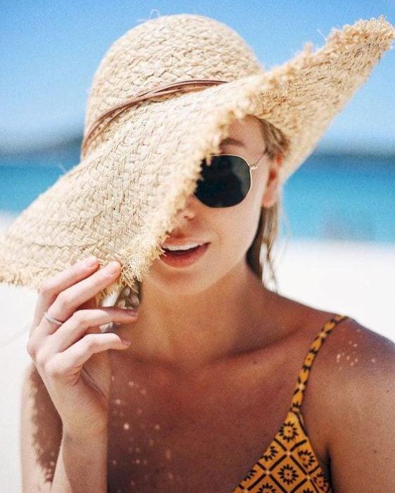 Chica en la playa cubriendo medio rostro con un sombrero