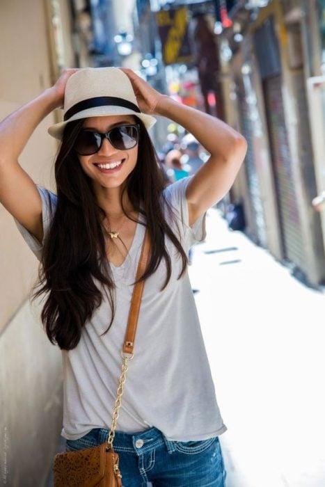 Chica sonriendo y sosteniendo su sombrero color gris con ambas manos