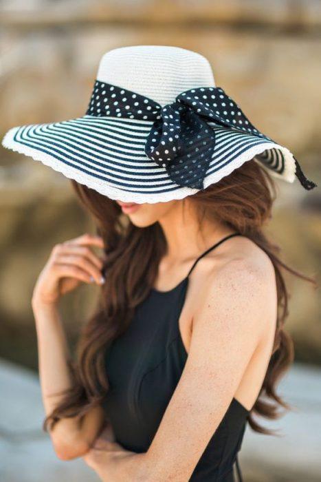 Chica cubriendo su rostro con un sombrero grande a rayas negras