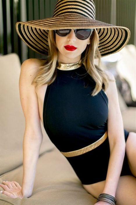 Chica sentada en un sofá playero usando sombrero grande a rayas negras