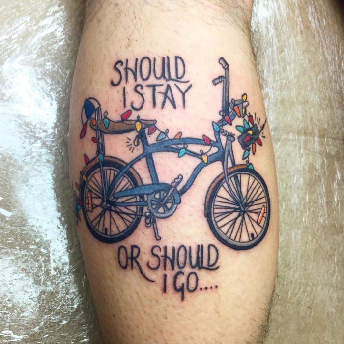 Tatuaje inspirado en Stranger Things con una bicicleta como la de Will y una serie de focos de colores