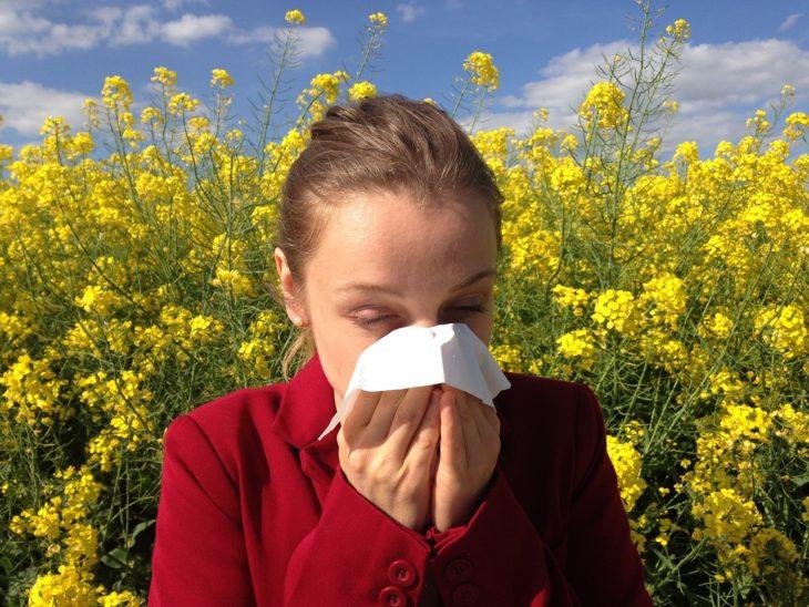 una mujer en un campo de flores se suena la nariz con un pañuelo blanco