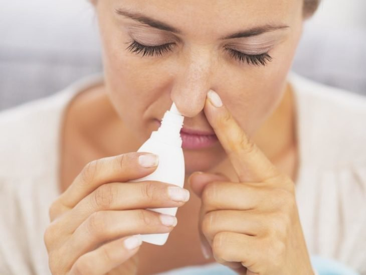 una mujer coloca gotas nasales en su nariz