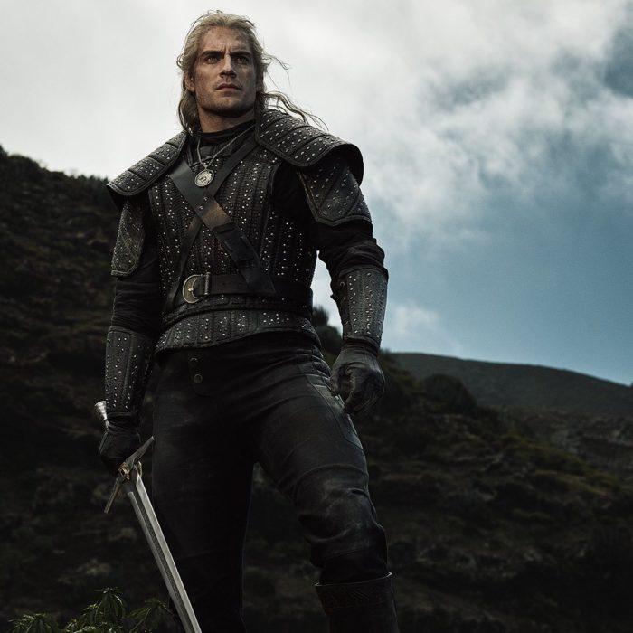 Henry Cavill como el hechicero Geralt de Rivia en serie de Netflix, The Witcher; hombre con cabello largo y blanco con armadura y espada