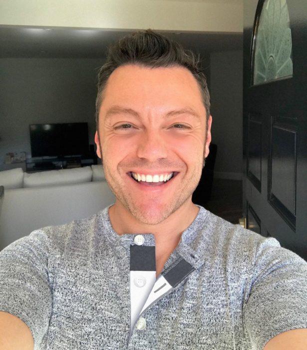 Tiziano ferro sonriendo feliz mientras se toma una selfie en su casa