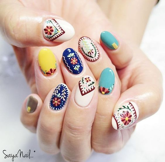 Uñas decoradas con esmaltes de colores vivos y efectos bordados