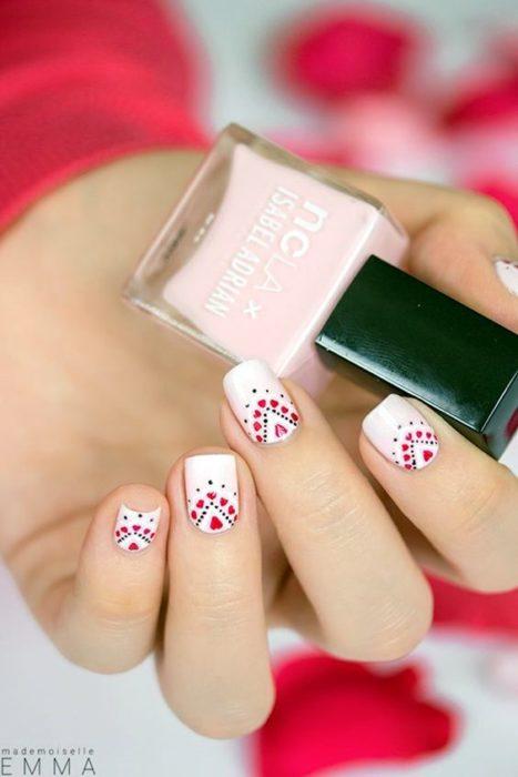 Uñas decoradas en blanco con pequeños puntos de colores rojos en efecto bordado