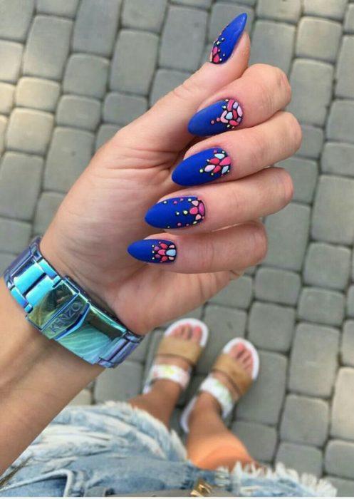 Uñas en color azul eléctrico decoradas con flores efecto bordado