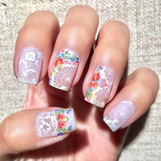 Uñas decoradas con flores de colores y diseños en blanco efecto borado