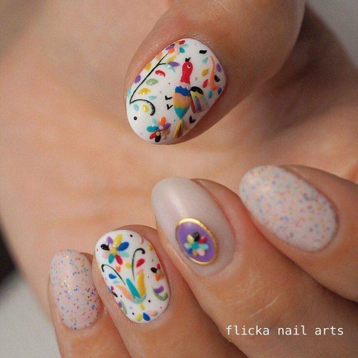 Uñas decoradas con diseños de aves de colores en efecto bordado