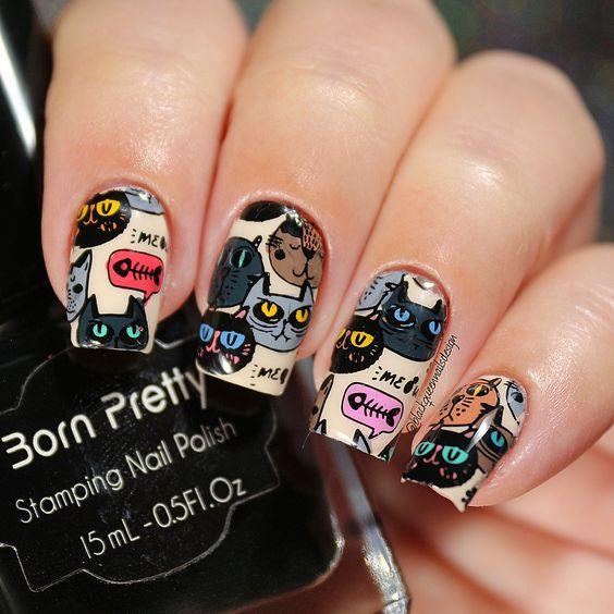 Mano de mujer con uñas decoradas con stickers de gatos oscuros