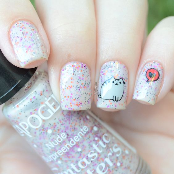 Mano de mujer con uñas pintadas en color rosa pastel con detalles de glitters en colores y un pequeño gato gris