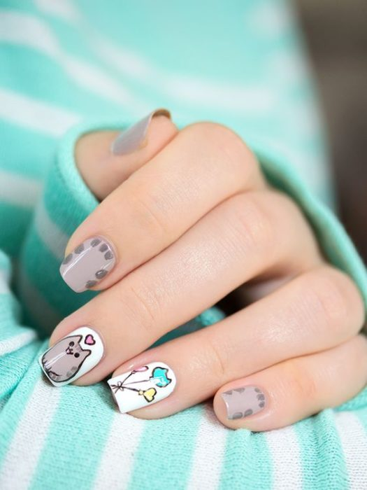 Mano de mujer con uñas pintadas en color girs claro y blanco con detalles en globos y gratos grisáceos