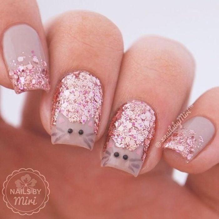 Mano de mujer con uñas pintadas en color rosa pastel con detalles en glitter y dibujos de gatos