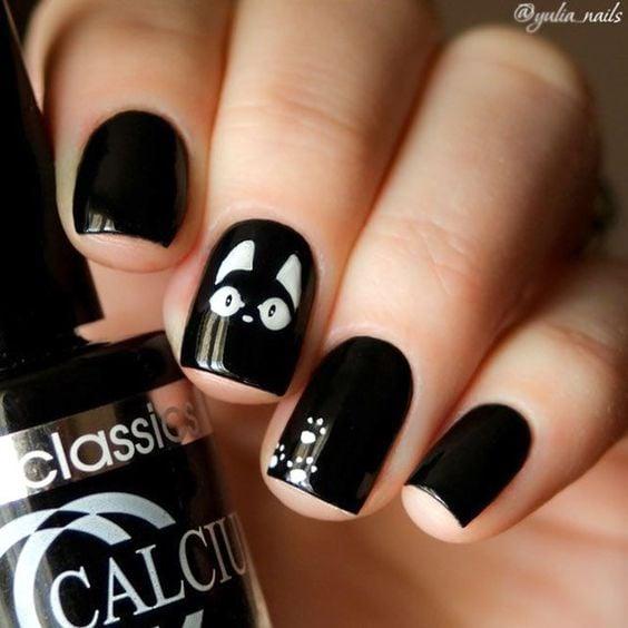 Mano de mujer con uñas pintadas en color negro con pequños detalles en blanco simulando un gato