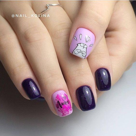 Mano de mujer con uñas pintadas en color morado con rosa pastel y un gato dibujado en blanco