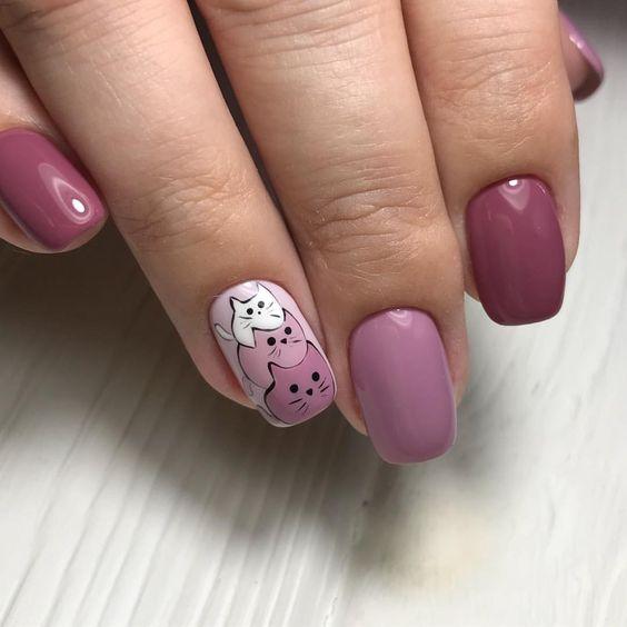 Mano de mujer con uñas pintadas en color rosa pastel y fuscia con detalles en gatos pequeños
