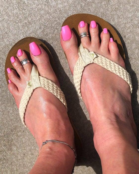 Chica con las uñas de los pies acrílicas en color rosa