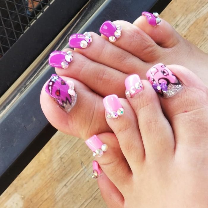 Chica con unas uñas largas acrílicas en color rosa con piedras