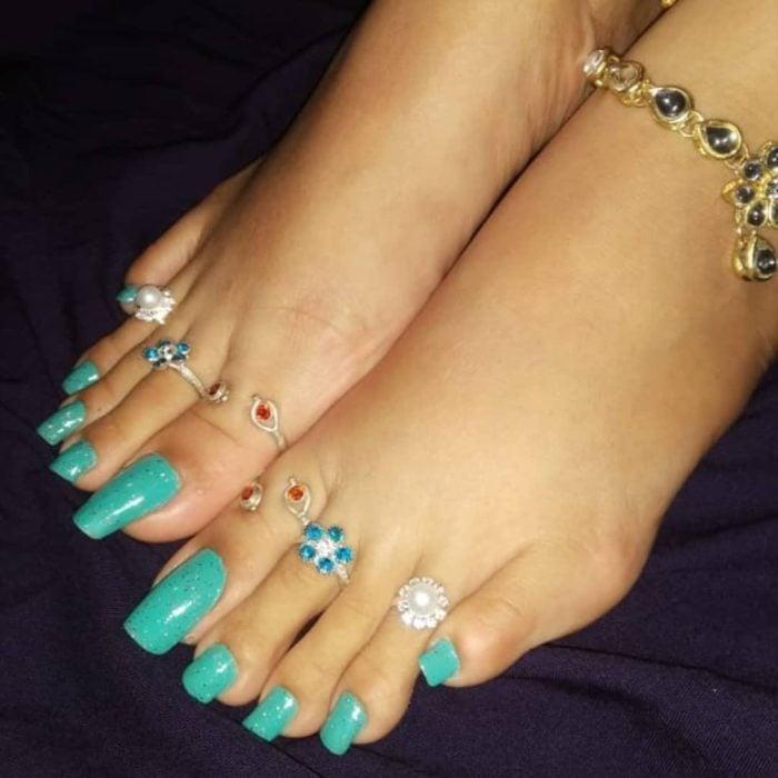 Chica con uñas acrílicas de color azul en los pies