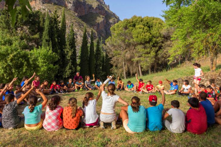 niños en una actividad al aire libre en la sierra hacen un círculo sentados