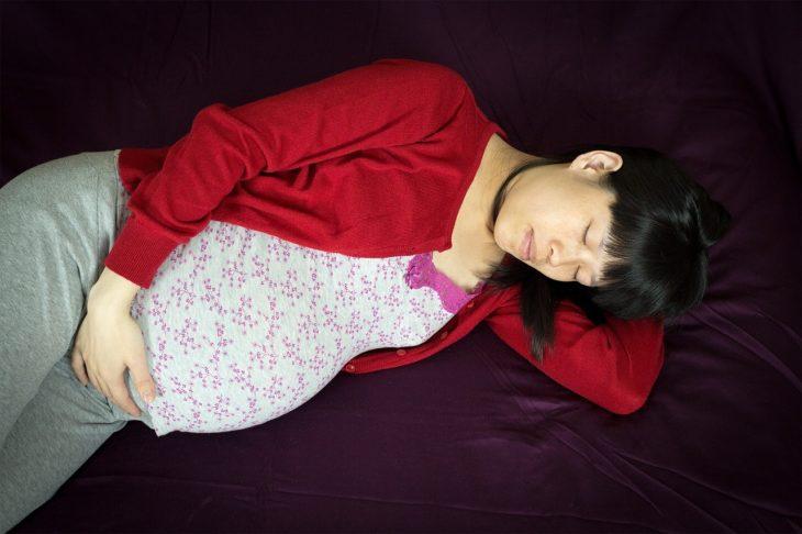 mujer asiática embarazada acostada