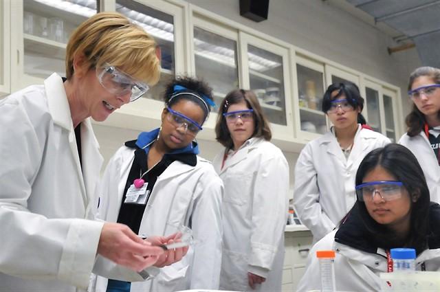 varias mujeres en bata de laboratorio observan algo en un laboratorio
