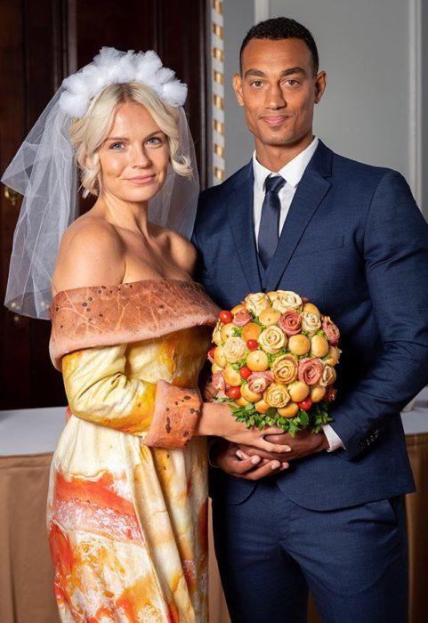 Chica usando un vestido de novia con estampado de pizza y un ramo de carnes frías con pan