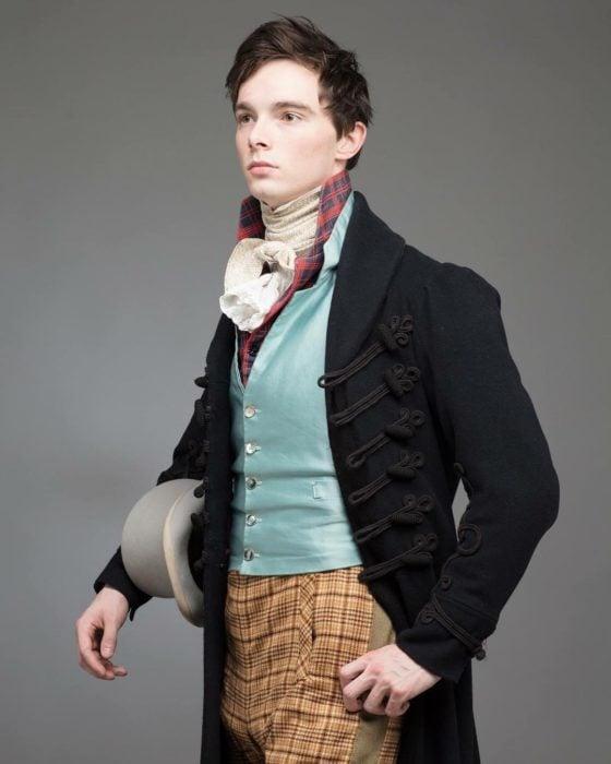 Zack Pinsent, chico que viste ropa vintage de 1820; hombre con vestimenta antigua, saco negro con ornamentos, chaleco azul aqua y pantalones amarillos con cuadros
