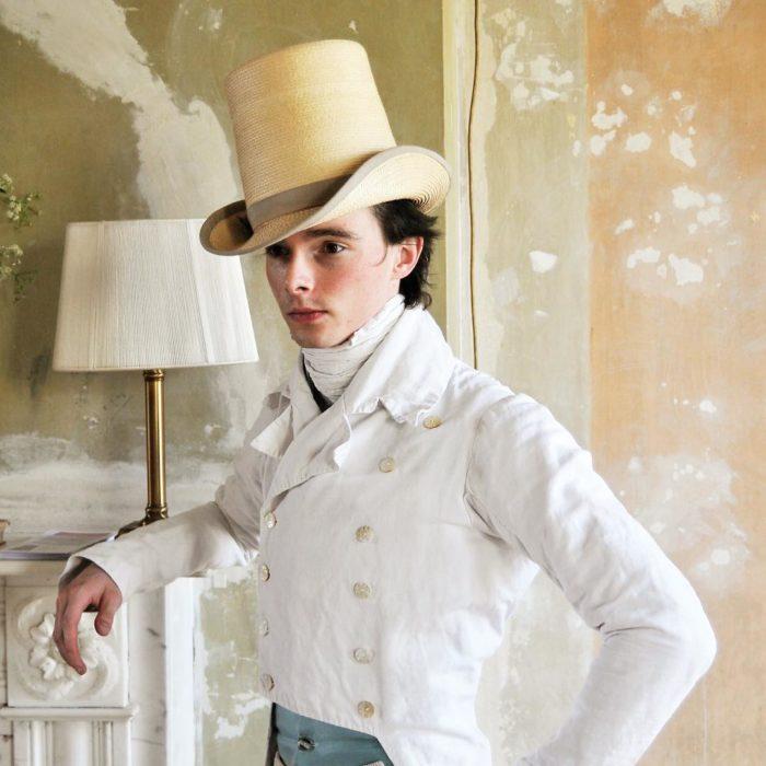 Zack Pinsent, chico que viste ropa vintage de 1820; hombre con vestimenta antigua, saco blanco con doble hilera de botones y sombrero de copa de mimbre